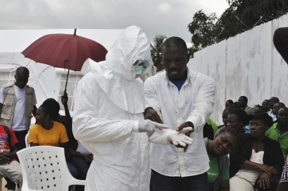 A volunteer health worker practises using a PPE suit at a newly-constructed Ebola virus treatment centre in Monrovia, Liberia