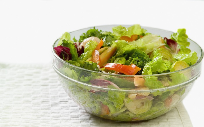 Bowl of salad with shrimp and vegetables sitting on a paper towel, close-up, part of